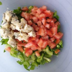 Voeg de gorgonola toe aan de kom met de tomaat en bleekselderij.